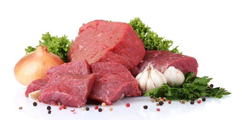 Morceaux de bœuf crus avec du poivre et de l'oignon et de l'ail